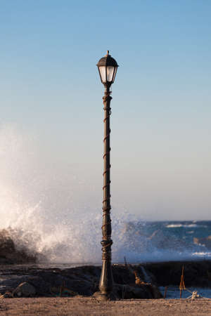lamp post: Old streetlamp near the sea. Oia village, Santorini island, Greece