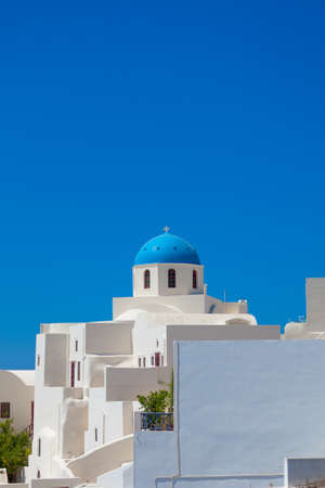 A beautiful white church with blue dome against blue sky in Oia, Santorini island, Greece photo