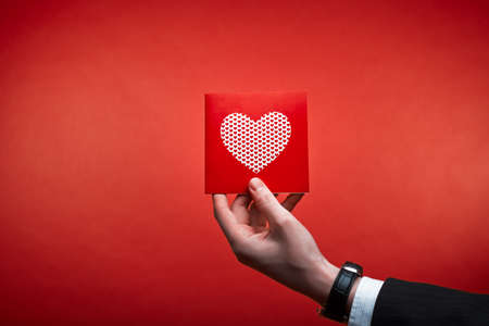 Male hand holding red Valentines card with heart on a pink background Stock Photo