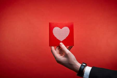 Mano masculina que sostiene la tarjeta roja de San Valentín con el corazón en un fondo de color rosa