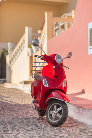 land transportation: Red italian scooter parked on the street in Oia village, Santorini, Greece  Stock Photo