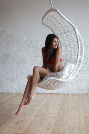 Beautiful woman sitting in a modern swing chair photo