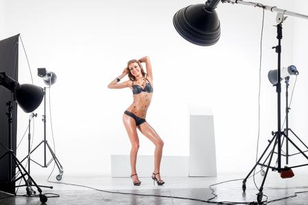 Jonge positieve vrouw poseren in professioneel uitgeruste fotostudio