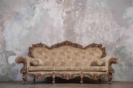 古い漆喰背景にアンティークのソファ 写真素材