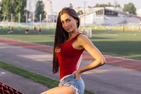 Young woman posing at local stadium during the soccer game