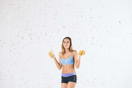 Fitness woman eating bananas. Healthy diet eating concept.