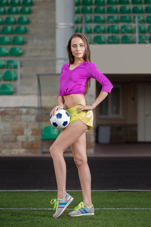Young and beautiful fitness woman posing on playing field with football or soccer ball