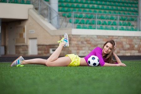Sexy fitness woman or cheerleader in bright outfit laying on the playing field with a soccer ball