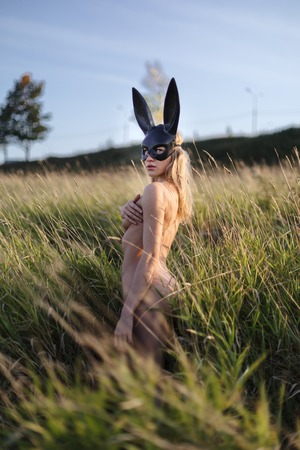 Beautiful naked woman wearing black fashion bunny mask posing in grass at the field.