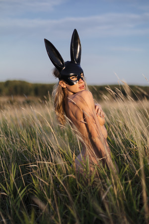 Beautiful woman wearing black fashion bunny mask posing in grass at the field.