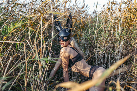 Beautiful woman wearing black fashion bunny mask posing in thickets.