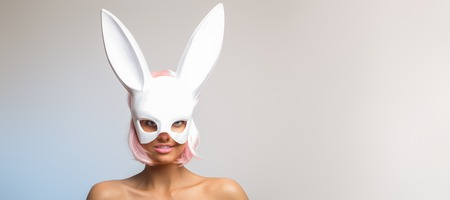 Young and fresh spring easter bunny with pink lips and hair. Pretty positive girl in whihe rabbit mask.