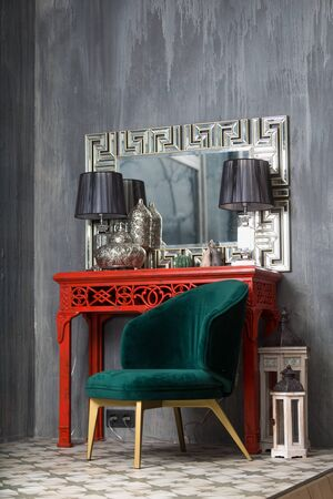 Green retro chair near the red dressing table with ornamented mirror and lamps Фото со стока