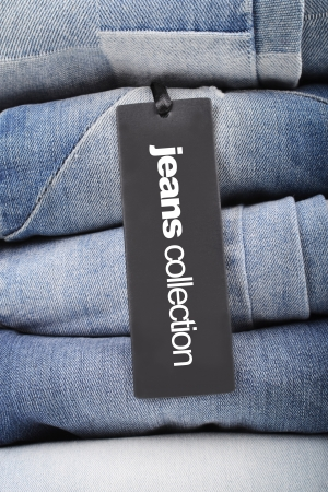 clothing tag: stack of folded jeans with tag Stock Photo
