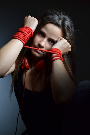 woman tied:  beautiful young woman tied with the red rope, studio shot