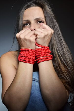 bonding rope:  beautiful young woman tied with the red rope, studio shot