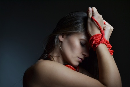 bondage woman:  beautiful young woman tied with the red rope, studio shot