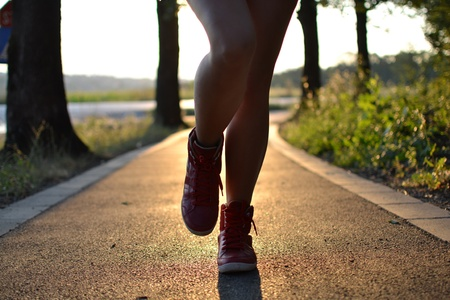 young woman walking in the park , legs close up photo