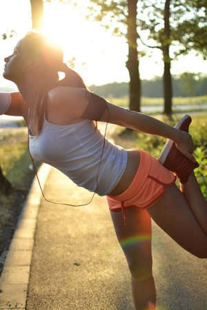 young woman working out in the park at sunset or sunrise photo