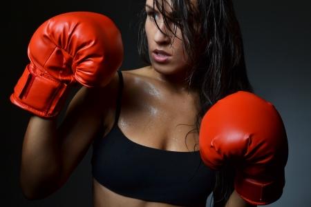 sudoracion: mujer hermosa con los guantes de boxeo rojos, tiro del estudio