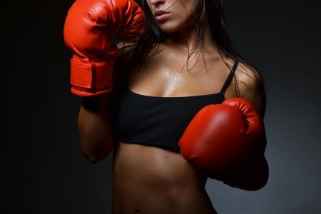 mujer deportista: mujer hermosa con los guantes de boxeo rojos, tiro del estudio