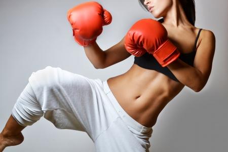 fitness: mujer hermosa con los guantes de boxeo rojos, tiro del estudio