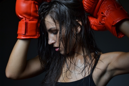 sweating: beautiful woman with the red boxing gloves, studio shot Stock Photo