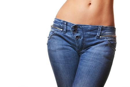 abdomen plano: el primer tiró de los pantalones vaqueros que desgastan femeninas, aisladas sobre fondo blanco