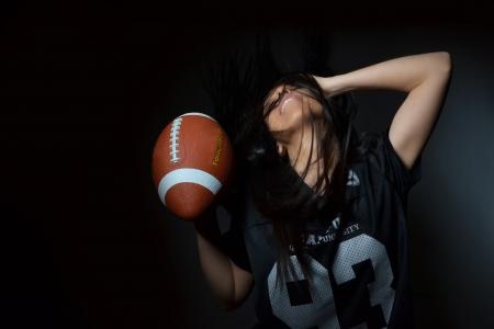 美しい若い女性が、アメリカン フットボールのコンセプト スタジオ撮影