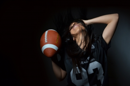 beautiful young woman, american football concept, studio shot  Stock Photo