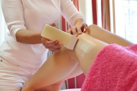 woman having her legs waxed in spa salon photo