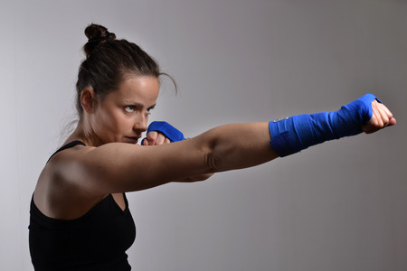 modern fighter: fitness woman boxing, studio shot