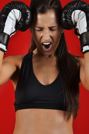 beautiful fitness woman with the black boxing gloves, against the red background photo