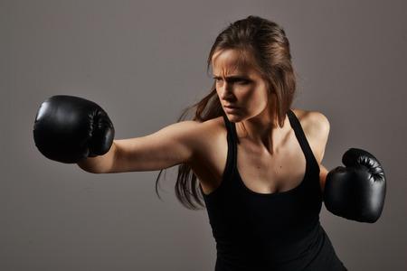 黒いボクシング グローブを持つ美しいフィットネス女性