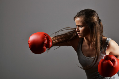 beautiful fitness woman with the red boxing gloves Фото со стока