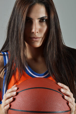 beautiful woman with the basketball, studio shot photo