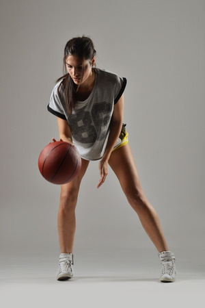 girl in shorts: beautiful woman with the basketball, studio shot