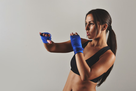 kickboxing: fitness woman with the blue boxing bandages, studio shot