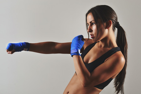 girl punch: fitness woman with the blue boxing bandages, studio shot