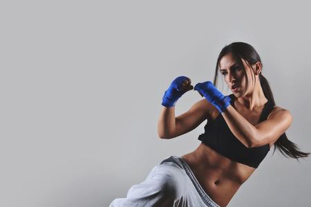 boxer: Mujer de la aptitud con las vendas de boxeo azules, tiro del estudio