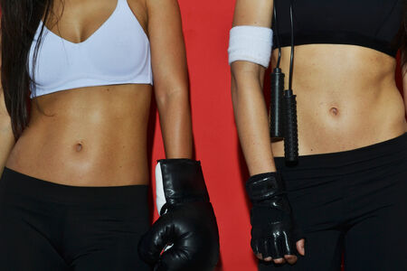 Fitness women posing against red background, close up Stock Photo