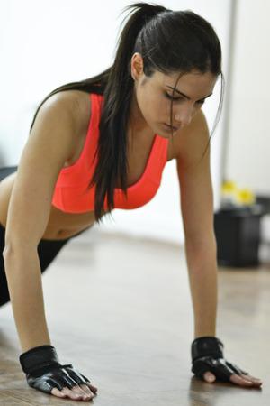 Schöne junge Frau arbeitet im Fitness