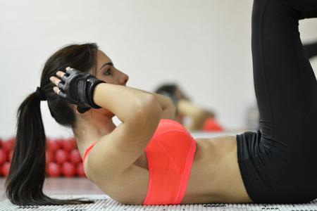 Schöne junge Frau arbeitet im Fitnessstudio