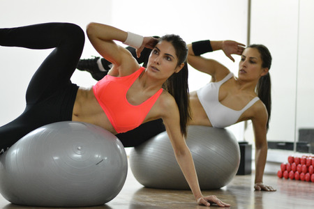 Beautiful young women working out in the fitness studio