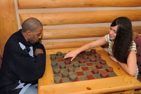 African American Father and Daughter Playing Checkers