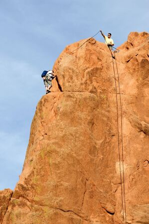 Rock Climber climbing a cliff photo
