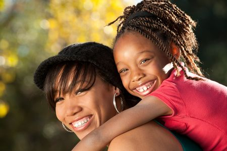 Happy African American mother and child having fun spending time together in a park photo
