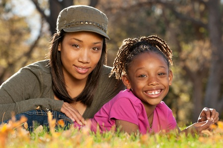 African American mother and child having fun spending time together in a park photo