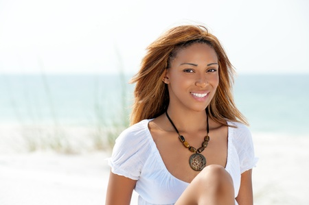 Happy African American young woman relaxing on the beach