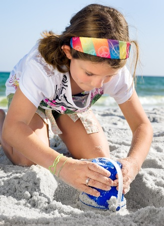 children sandcastle: Happy girl building sandcastle on a beach